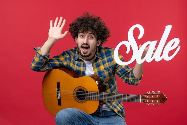 Vista frontale giovane maschio seduto con la chitarra sulla vendita di un muro rosso suona musica da concerto applausi musicista dal vivo colore