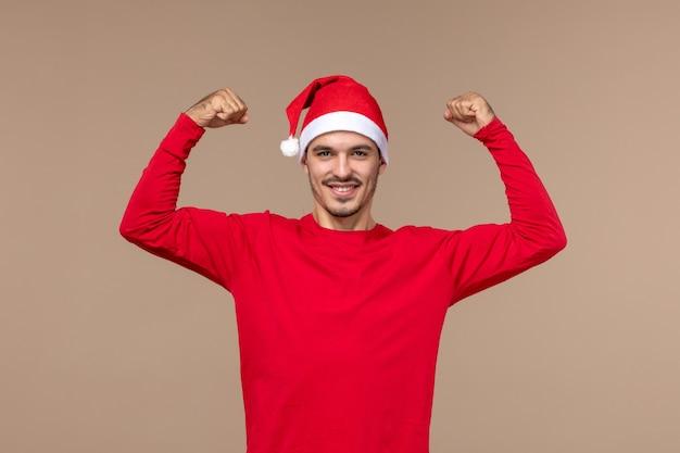 Вид спереди молодой мужчина улыбается и сгибается на коричневом фоне эмоции рождественского праздника