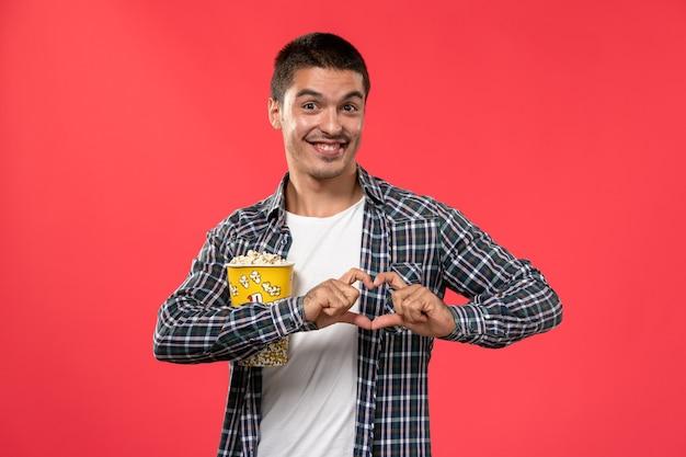 전면보기 젊은 남성 미소하고 밝은 붉은 벽 시네마 극장 영화 남성 영화에 팝콘 패키지를 들고