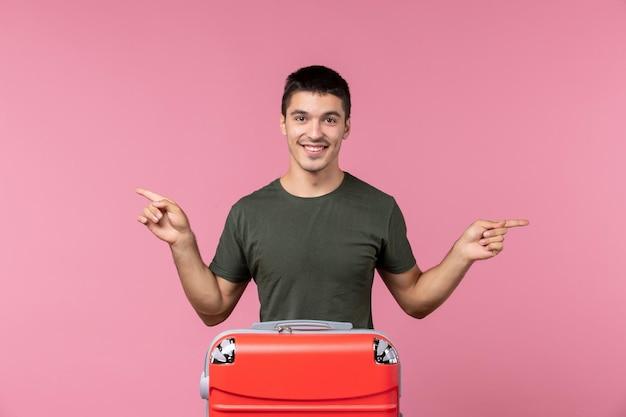 Вид спереди молодой мужчина улыбается и готовится к отпуску с большой сумкой на розовом пространстве