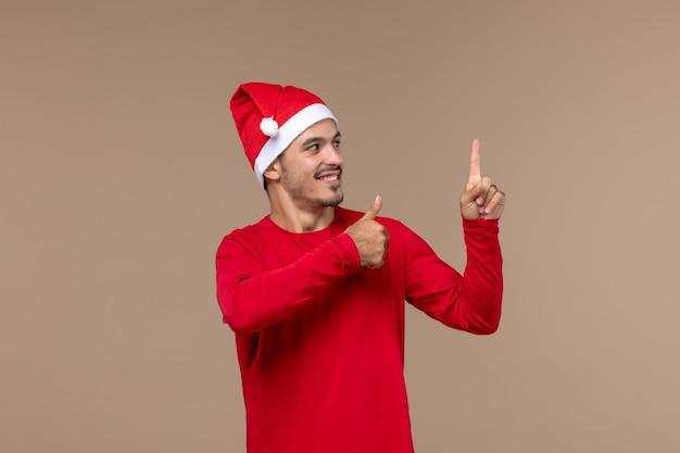 Вид спереди молодой мужчина улыбается на коричневом фоне рождественские эмоции праздник мужчина