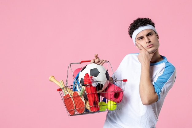 Front view young male in sport clothes with basket full of sport things pink wall