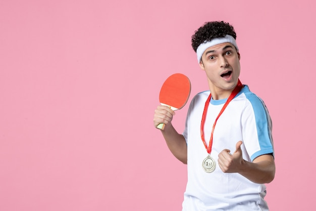 Giovane maschio di vista frontale in vestiti di sport con la racchetta e la medaglia sulla parete rosa