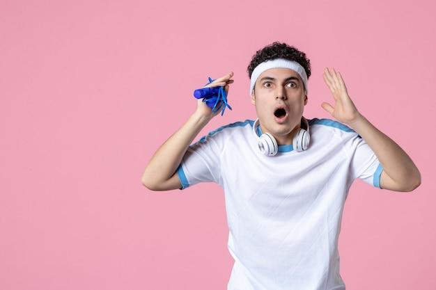 Giovane maschio di vista frontale in vestiti di sport con la corda per saltare sulla parete rosa