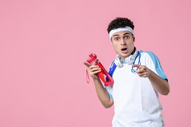 Vista frontale giovane maschio in abiti sportivi con corda per saltare e parete rosa acqua