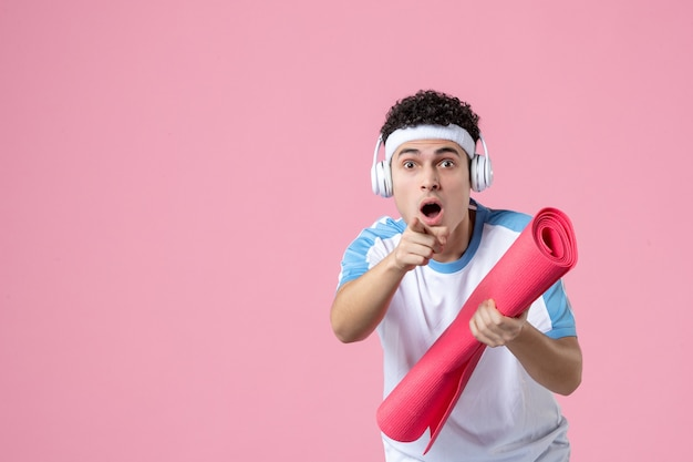 Front view young male in sport clothes with yoga mat on pink wall
