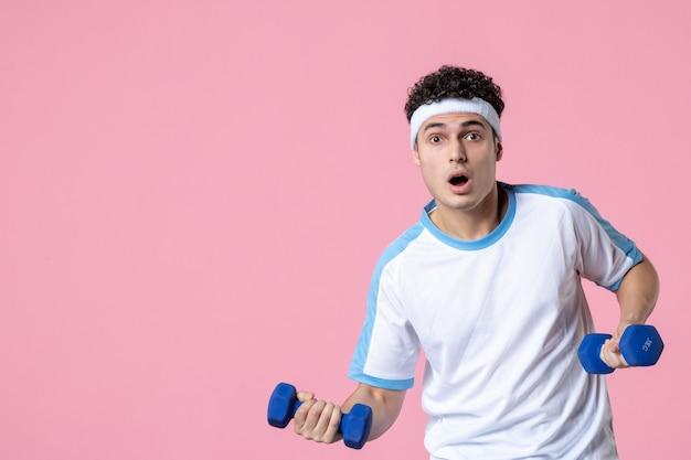 Giovane maschio di vista frontale in vestiti di sport che risolve con i dumbbells sulla parete rosa