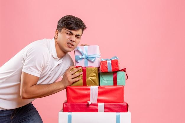 Вид спереди молодой мужчина, стоящий вокруг рождественских подарков на розовом фоне