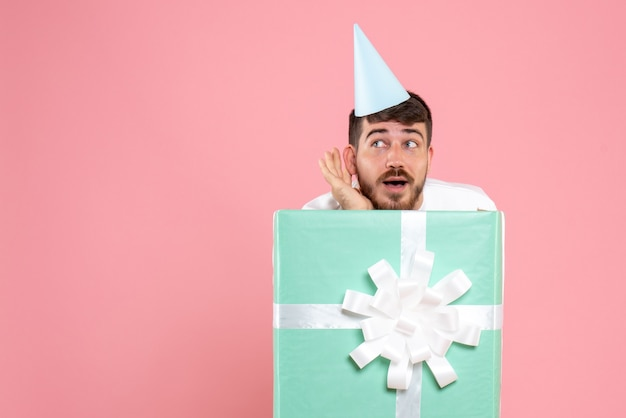 Front view young male standing inside present box on light pink color human emotion xmas photo pajama party