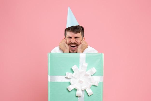 Вид спереди молодой мужчина, стоящий внутри подарочной коробки на светло-розовом цвете рождественской фото эмоции пижамной вечеринке