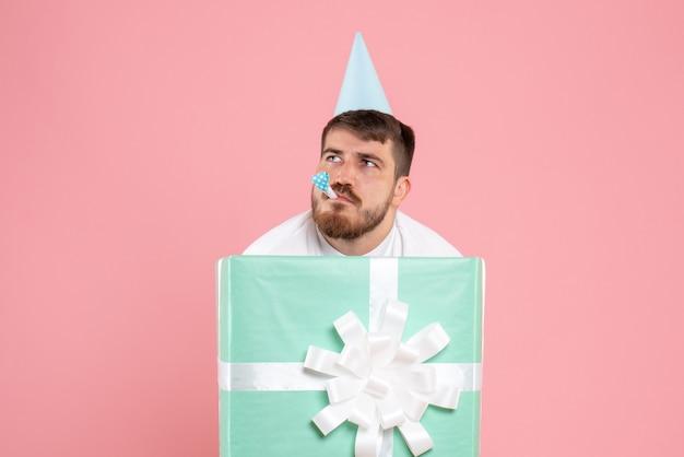 Вид спереди молодой мужчина, стоящий внутри подарочной коробки на розовой пижамной вечеринке, фото эмоции, сон, рождество