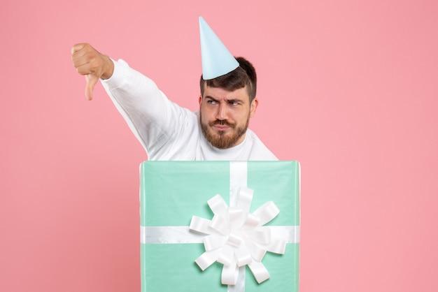 ピンクのクリスマスの写真の色の感情のパジャマパーティーのプレゼントボックスの中に立っている正面図若い男性