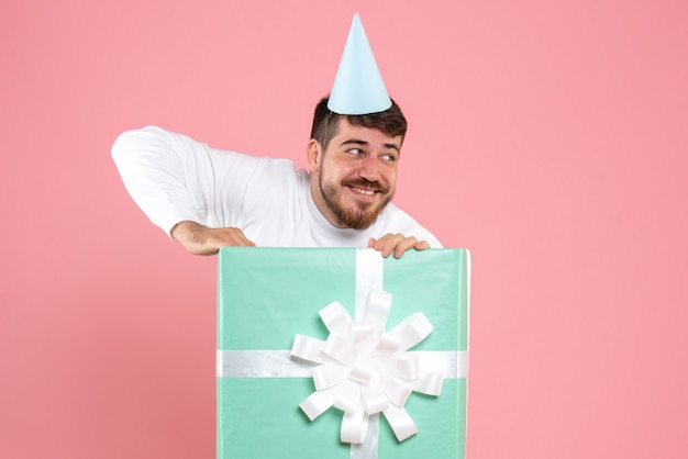 Front view young male standing inside present box on pink color emotion xmas photo human pajama party