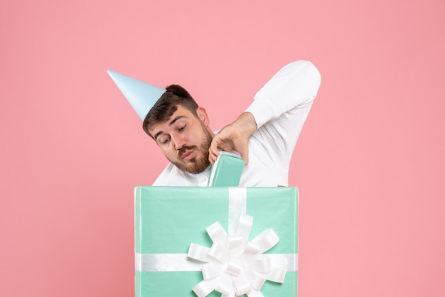 Front view young male standing inside present box on pink color pajama party photo emotion sleep xmas