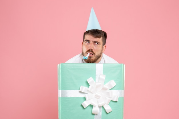 Front view young male standing inside present box on pink color pajama party photos emotion sleep xmas