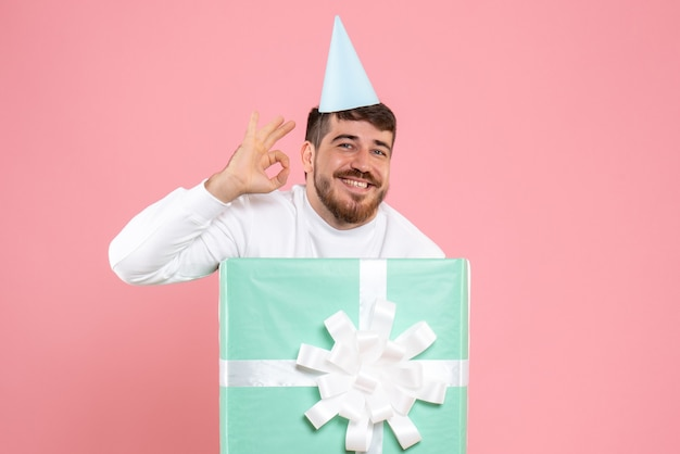 Front view young male standing inside present box on the pink photo color emotion xmas pajama party