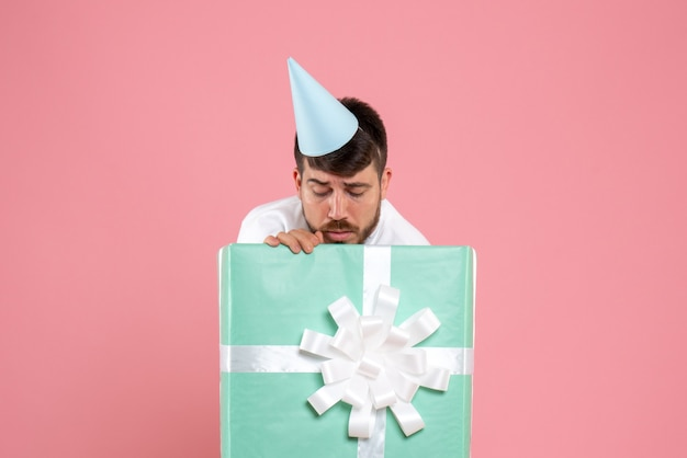 Front view young male standing inside present box on pink photo color human emotion xmas pajama party