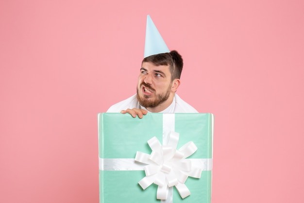 Front view young male standing inside present box on the pink xmas photo color emotion pajama party