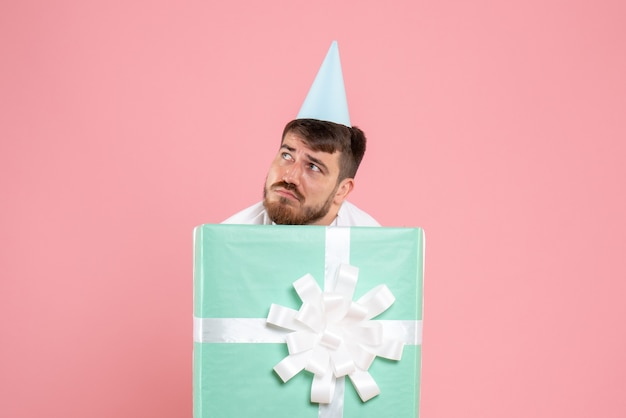 Front view young male standing inside present box stressed on pink color pajama party photo emotion sleep xmas