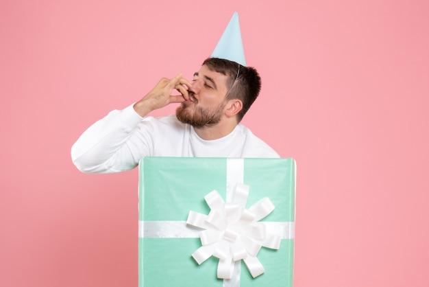 Vista frontale giovane maschio in piedi all'interno della scatola attuale con la faccia felice sulla foto rosa colore emozione xmas pigiama party