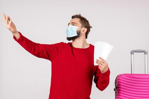 Giovane maschio di vista frontale nella mascherina sterile che tiene i biglietti sul colore di viaggio di volo del virus di vacanza di covid-aereo della parete bianca