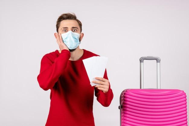 Giovane maschio di vista frontale nella maschera sterile che tiene i biglietti sui voli del virus di emozione di colore di viaggio di viaggio di covid-viaggio della parete bianca