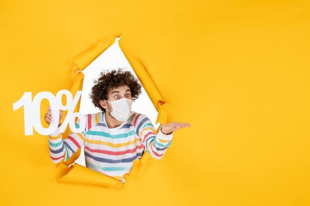 Vista frontale giovane maschio in maschera sterile che tiene la scrittura su foto gialla vendita pandemica di coronavirus covid