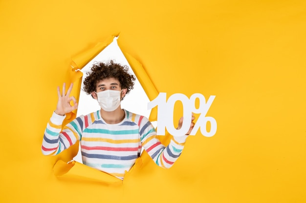 Front view young male in sterile mask holding writing on a yellow photo health covid coronavirus human pandemic sale