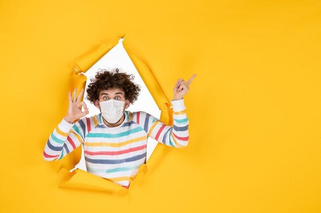 Vista frontale giovane maschio in maschera sterile su foto a colori gialla covid- virus pandemico sanitario umano