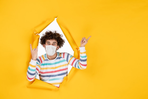 Front view young male in sterile mask on yellow color photo covid- health virus human