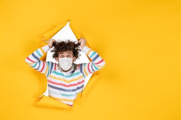 Vista frontale giovane maschio in maschera sterile su scrivania gialla colore sanitario covid pandemia virus foto umana human