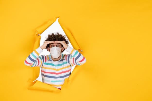 Vista frontale giovane maschio in maschera sterile su pandemia umana di colore giallo strappato covid-salute