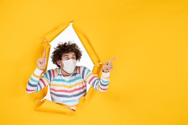 Vista frontale giovane maschio in maschera sterile su virus pandemico della foto umana di colore giallo strappato covid-