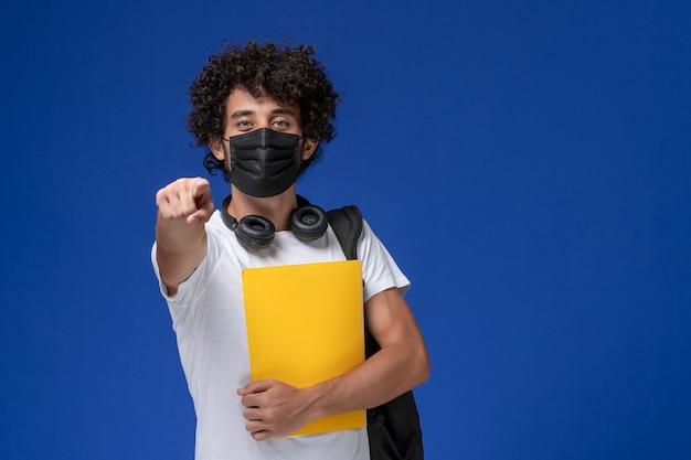 Вид спереди молодой студент-мужчина в белой футболке в черной маске и с желтыми файлами на голубом фоне.