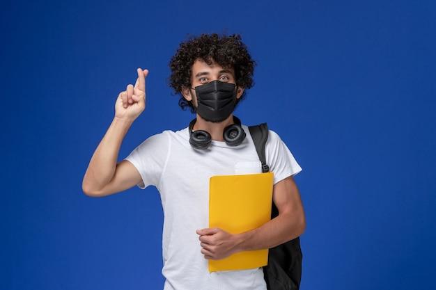 黒のマスクを身に着けて、水色の机の上に黄色のファイルを保持している白いtシャツの正面図若い男子生徒。