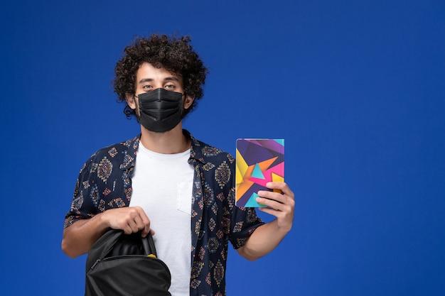 正面図黒のマスクを身に着けて、水色の背景にバックパックのコピーブックを保持している若い男子学生。