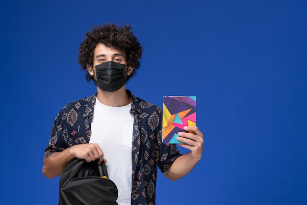 Front view young male student wearing black mask and holding backpack copybook on light-blue background.