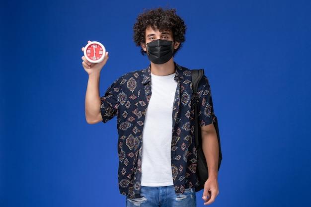 Вид спереди молодой студент-мужчина в черной маске с рюкзаком, держащим часы на синем фоне.