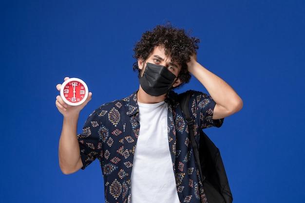 青い机の上に時計を保持しているバックパックと黒いマスクを身に着けている正面図の若い男子生徒。