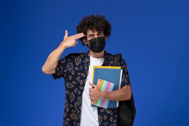 正面図青の背景にコピーブックとファイルを保持しているバックパックと黒のマスクを身に着けている若い男子学生。