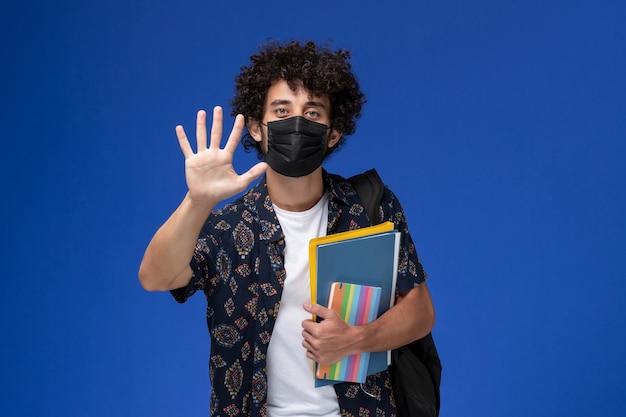 青い机の上にコピーブックとファイルを保持しているバックパックと黒いマスクを身に着けている正面図の若い男子生徒。