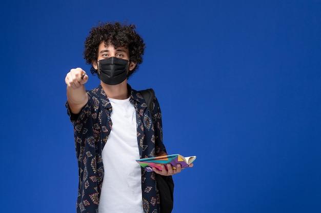 파란색 배경에 카피 북과 펜을 들고 배낭에 검은 마스크를 쓰고 전면보기 젊은 남성 학생.