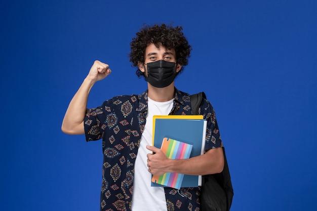 Vista frontale giovane studente maschio che indossa la maschera nera con zaino in possesso di quaderno e file che si rallegrano su sfondo blu.