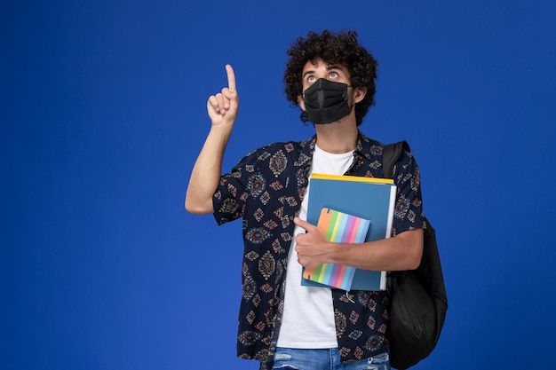 Vista frontale giovane studente maschio che indossa la maschera nera con zaino in possesso di quaderno e file pensando su sfondo blu.