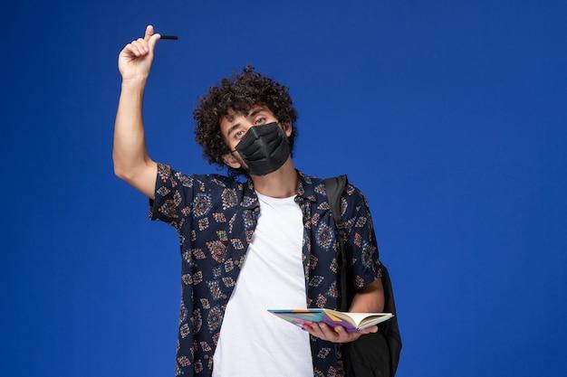 青い背景にコピーブックを保持しているバックパックと黒のマスクを身に着けている正面図若い男子学生。
