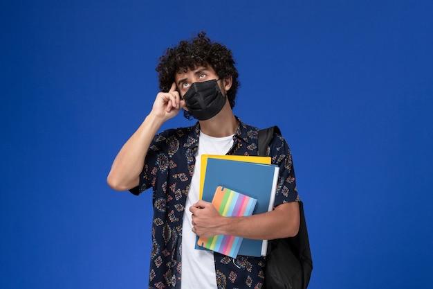 青い机の上でファイルとコピーブック思考を保持しているバックパックと黒いマスクを身に着けている正面図の若い男子生徒。