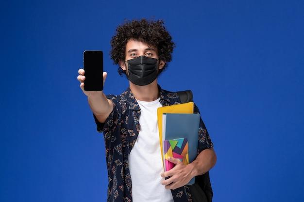 青い背景にファイルと電話を保持しているバックパックと黒いマスクを身に着けている正面図若い男子学生。