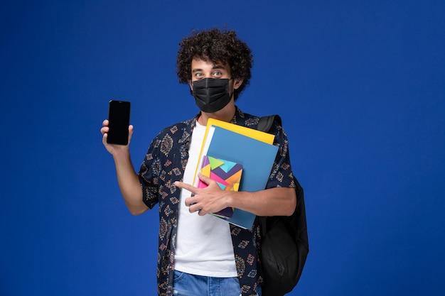 青い机の上にファイルと電話を保持しているバックパックと黒いマスクを身に着けている正面図の若い男子生徒。