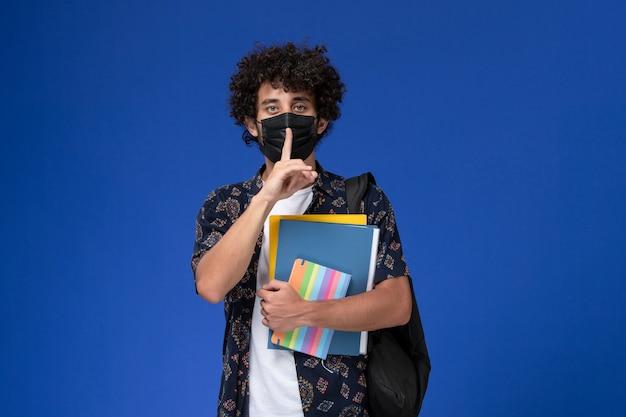 Vista frontale giovane studente maschio che indossa la maschera nera con zaino in possesso di file e quaderno su sfondo blu.