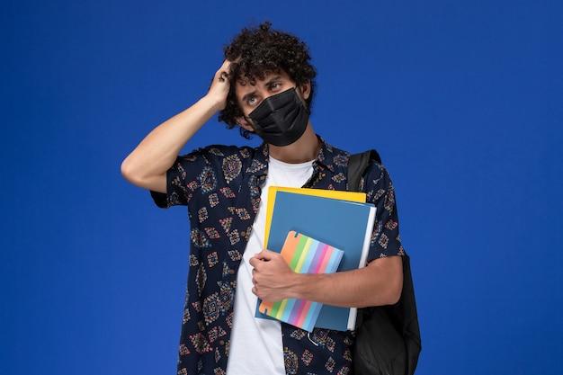 Vista frontale giovane studente maschio che indossa la maschera nera con zaino in possesso di file e quaderno pensando sullo sfondo blu.